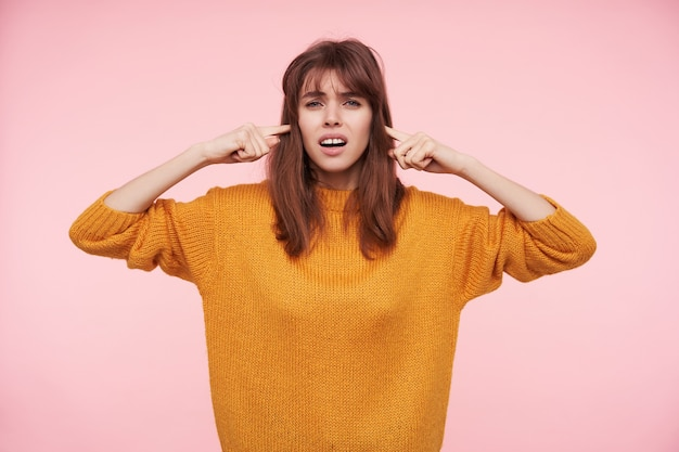 Binnenfoto van ontevreden jonge brunette dame die haar oren sluit en haar wenkbrauwen fronst terwijl ze kijkt, casual kleding draagt terwijl ze poseren over roze muur