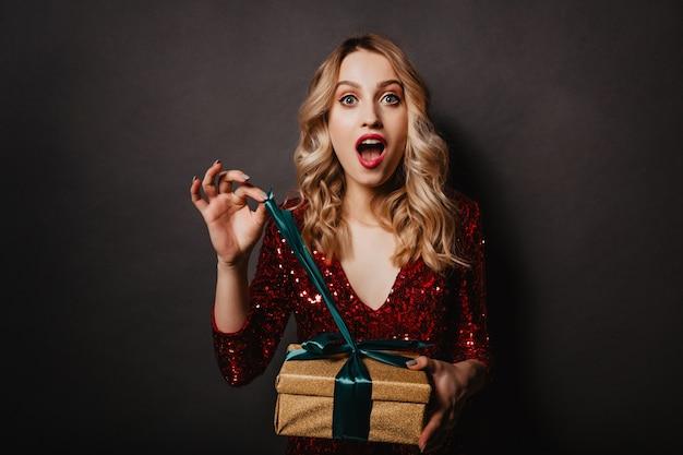 Binnenfoto van opgewonden jonge dame die haar cadeau opent