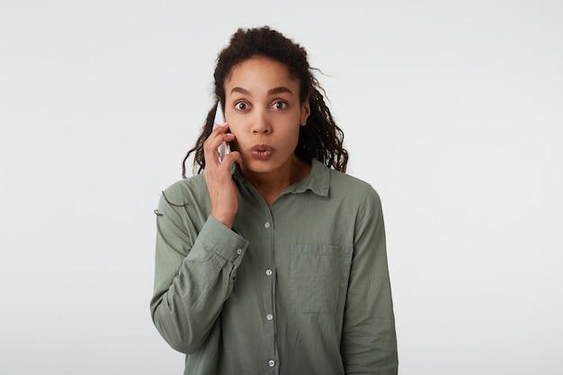 Binnenfoto van opgewonden jonge donkerharige krullende vrouw met natuurlijke make-up die verrast haar bruine ogen rondt terwijl ze telefoneert, geïsoleerd op witte achtergrond