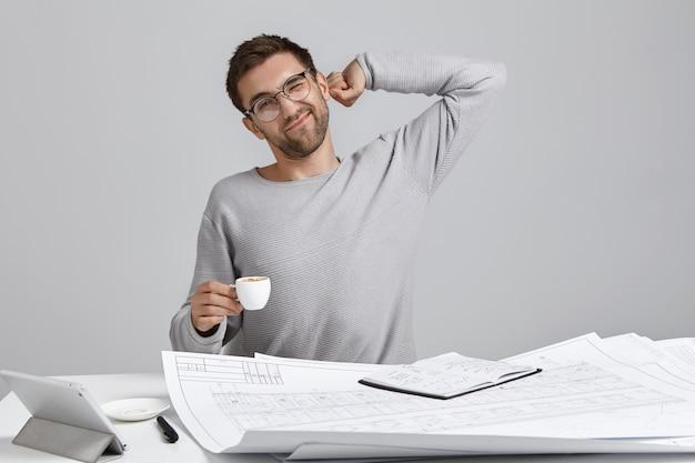 Binnenfoto van overwerkte mannelijke creatieve ontwerper, strekt zich uit terwijl hij aan tafel zit,