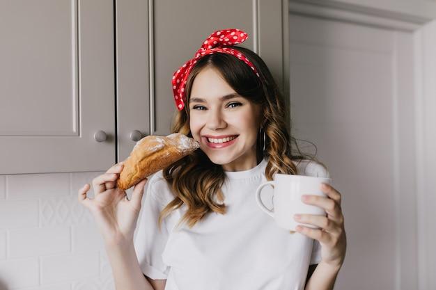 Binnenfoto van prachtig meisje dat zoete croissant eet. portret van geweldige europese dame met plezier tijdens de lunch.