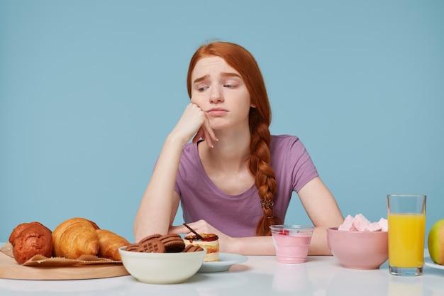 Binnenfoto van roodharig meisje dat met verdriet en ontevredenheid kijkt over het bakken van producten, denkt aan dieet