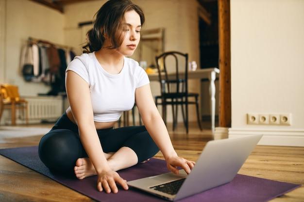 Binnenfoto van schattige plus size jonge vrouw zittend op de mat voor opengeklapte laptop, kijken naar online videozelfstudie door professionele fitnessinstructeur, trainen vanuit huis vanwege sociale afstand