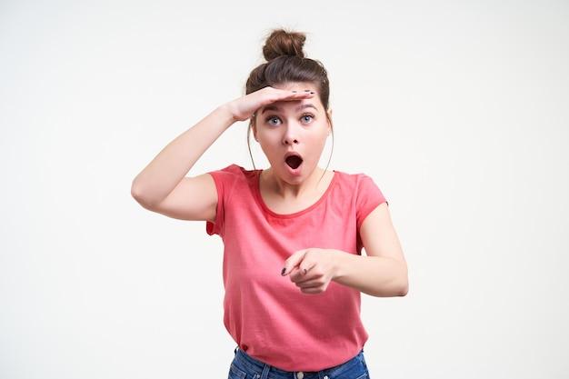 Binnenfoto van verbaasde jonge mooie brunette vrouw die hand op haar voorhoofd opheft en haar blauwe ogen verrast terwijl ze naar de camera wijst, geïsoleerd op witte achtergrond