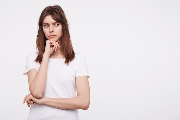 Binnenfoto van verwarde jonge donkerharige dame met casual kapsel, kin op opgeheven hand en fronsende wenkbrauwen terwijl ze serieus opzij kijkt, geïsoleerd over witte muur