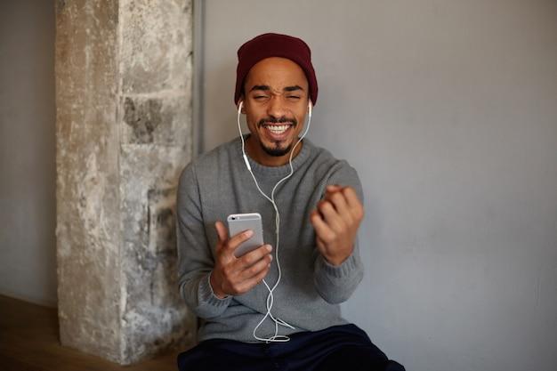 Binnenfoto van vrij positieve donkere man met baard, luisteren naar muziek met oortelefoons en meezingend lied, zijn perfecte witte tanden laten zien terwijl hij vrolijk glimlacht