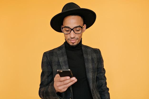 Binnenfoto van zwarte jonge man in prachtige kleding met smartphone. emotionele afrikaanse man wacht op oproep met glimlach.