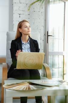 Binnenhuisarchitect die in modern bureau werkt. jonge zakenvrouw in eigentijds interieur. concept van zaken, zakenvrouw in de moderne samenleving, creatieve werkplek.