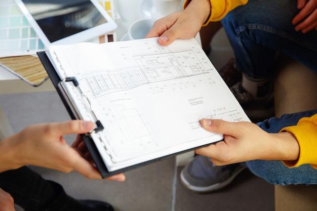Binnenhuisarchitect die met jong stel werkt. mooie familie en professionele ontwerper of architect bespreken concept van toekomstig interieur, werken met kleurenpalet, kamertekeningen in modern kantoor.