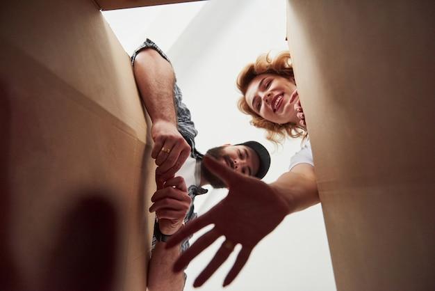Binnenkant van de doos. gelukkig paar samen in hun nieuwe huis. conceptie van verhuizen