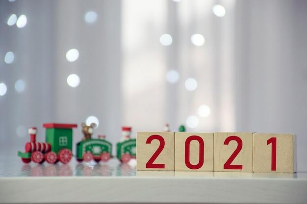 Binnenkort nieuwjaarsnummer op houten kubusblok met kleurrijke kersttrein en wazig bokeh lichten
