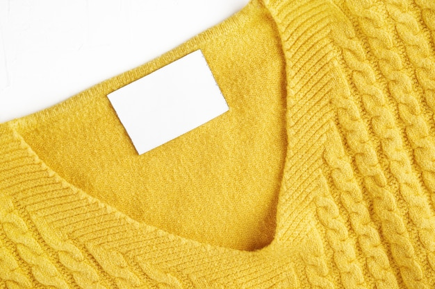 Binnenlabel met kopieerruimte op de hals van een gele wollen trui