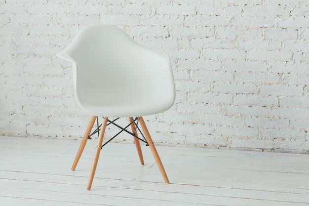 Binnenland met witte moderne stoel en een witte bakstenen muur