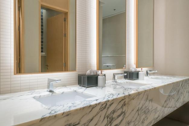 Binnenland van badkamers met wasbekkraan en zwarte handdoek in hotel.