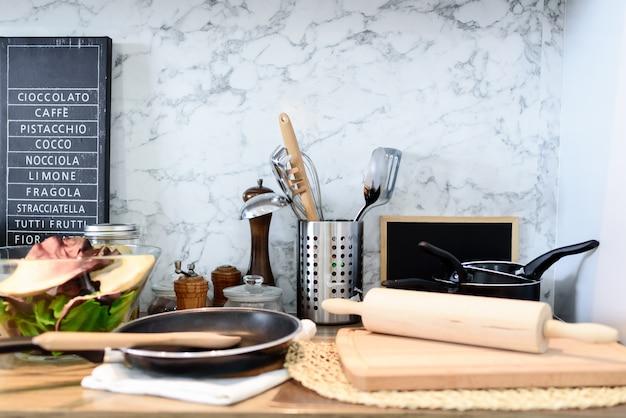 Binnenland van keukenruimte met reeks keukengerei op marmeren muur.