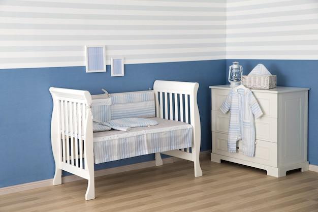 Binnenland van lichte comfortabele babyruimte met voederbak en beddegoed