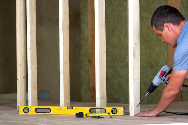 Binnenland van zolder geïsoleerde ruimte met eiken vloer onder wederopbouw. de jonge professionele arbeider gebruikt niveau en schroevedraaier die houten frame installeren voor toekomstige muren. renovatie en verbetering concept.