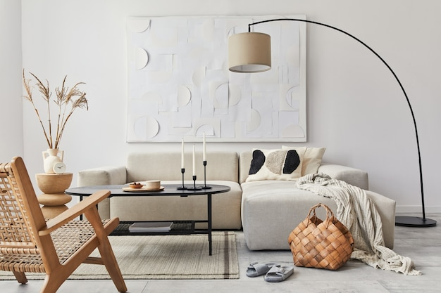 Binnenlands interieur van woonkamer met design modulaire bank, zwarte salontafel, lamp, fauteuil, decoratie, kunstschilderijen en elegante persoonlijke accessoires in modern interieur.
