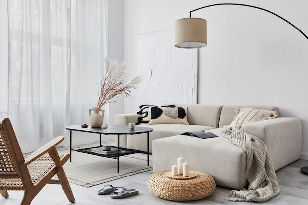 Binnenlands interieur van woonkamer met modulaire designbank, zwarte salontafel, lamp, decoratie, kunstschilderijen, poef, widnows en elegante persoonlijke accessoires in modern interieur..