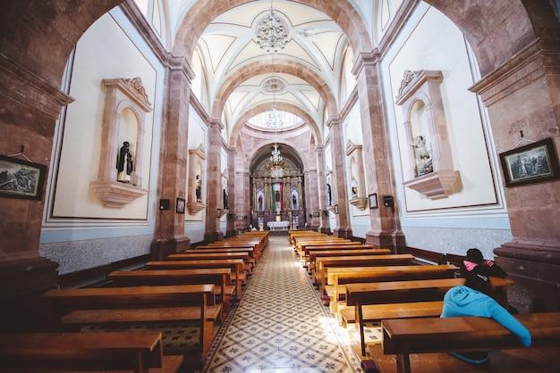 Binnenlands schot van een kerk met mensen die op de houten banken zitten