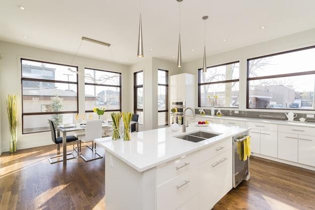Binnenlands schot van een moderne huiskeuken met grote vensters