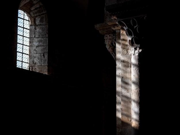 Binnenlands schot van een oud gebouw met de zon die door het venster over de pijler schijnt