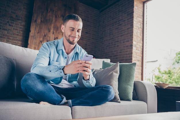 Binnenlandse knappe jongen thuisblijven quarantaine tijd telefoon vasthouden