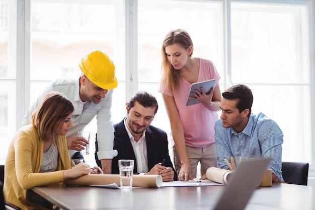 Binnenlandse ontwerper met collega's die blauwdruk bespreken