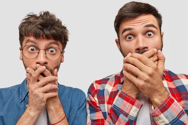 Binnenopname van aangenaam uitziende jonge twee bebaarde mannen die geschokte uitdrukkingen hebben doen schrikken, mislukking ontvangen, hun mond sluiten