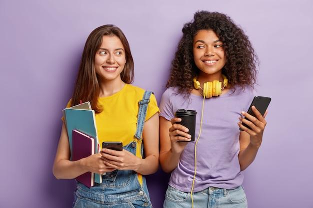 Binnenopname van aangenaam uitziende vrolijke twee groepsgenoten van gemengd ras hebben koffiepauze na de colleges