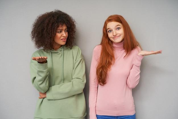 Binnenopname van aantrekkelijke jonge dames gekleed in vrijetijdskleding die hun handpalmen ophieven terwijl ze poseren over een grijze muur met verbaasde gezichten en de lippen gevouwen hielden