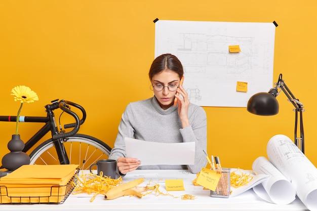 Binnenopname van bekwame vrouwelijke architect bespreekt ideeën voor engineeringproject via smartphone geconcentreerd in papier heeft rommel op de werkplek die betrokken is bij werkproces probeert project op tijd af te ronden