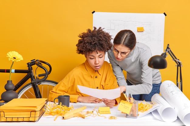 Binnenopname van bekwame vrouwen van gemengd ras, gefocust op papieren documenten, creëren aandachtig een nieuw project tijdens de werktijd in een coworking-ruimte. studenten bouwkunde controleren blauwdrukken
