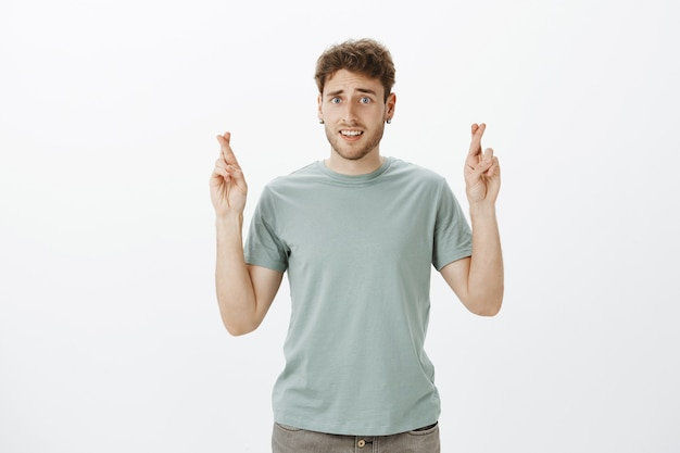 Binnenopname van bezorgde, onzekere knappe man met oorbellen, fronsend en onhandig glimlachend terwijl hij de vingers kruist en wensen doet of hoopt op promotie