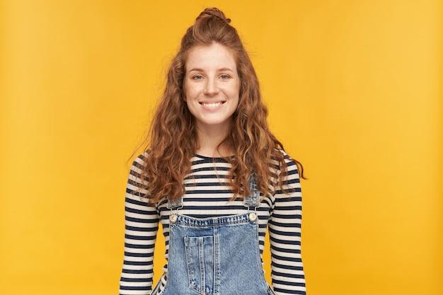 Binnenopname van charmante gembervrouw, draagt gestript shirt en spijkerbroek, kijkt naar voren terwijl ze breed glimlacht en haar witte tanden laat zien. geïsoleerd over gele muur