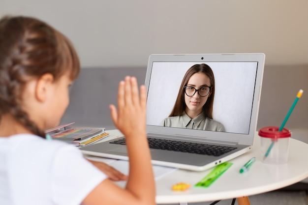 Binnenopname van donkerharig meisje met staartjes met een wit t-shirt, achterstevoren poserend, online les met leraar, kijkend naar display en zwaaiend met de hand, online afstandsonderwijs.