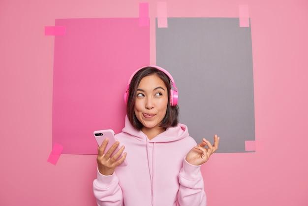 Binnenopname van dromerige aziatische vrouw likt lippen stelt zich iets voor terwijl ze luistert, favoriete muziek maakt gebruik van moderne technologieën, besteedt vrije tijd aan het genieten van nieuwe plylist-houdingen tegen lege kopieerruimte