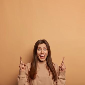 Binnenopname van een blij opgetogen vrouw wijst met beide wijsvingers naar boven, lacht vrolijk, adverteert met koele lege ruimte, draagt een losse trui