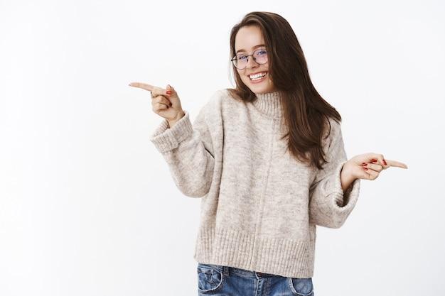 Binnenopname van een dwaze, zorgeloze en gelukkige aantrekkelijke jonge vrouw in een bril en trui die flirt en lacht terwijl ze zijwaarts naar rechts en links wijst, richting vragend en keuze makend over grijze muur.