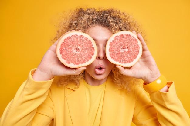 Binnenopname van een emotioneel verraste vrouw met krullend haar bedekt de ogen met plakjes grapefruit en houdt de mond geïsoleerd over een levendige gele muur. gewichtsverlies gezond eten veganistische levensstijl