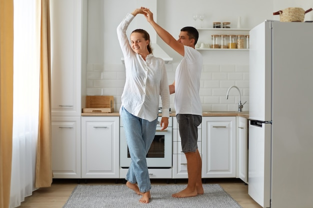 Binnenopname van een gelukkig stel dat plezier heeft in de keuken, samen danst, knappe jonge man die de hand van een mooie vrouw vasthoudt, naar favoriete muziek verhuist, samen van tijdverdrijf geniet.