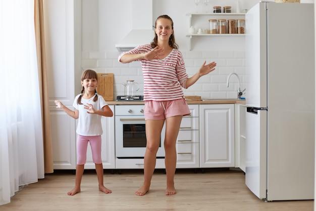 Binnenopname van een gelukkige positieve familie die gelukkig samen danst, dezelfde beweging maakt, naar de camera lacht, casual kleding draagt, kindertijd en ouderschap.
