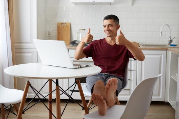 Binnenopname van een gelukkige positieve man die aan tafel in de keuken zit, met een glimlach naar een laoptop-display kijkt en duimen opsteekt, waarmee hij het idee van de werkgever over een nieuw project goedkeurt.