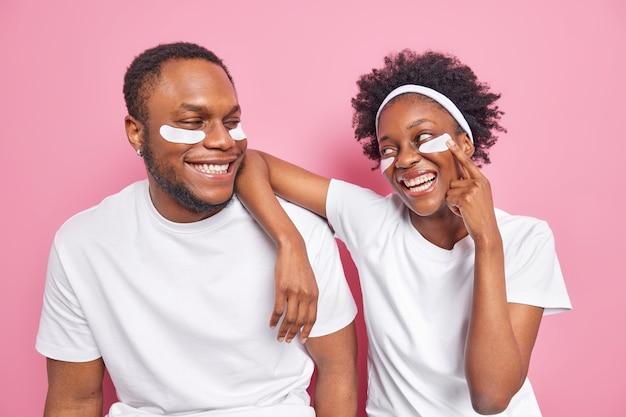 Binnenopname van een gelukkige zorgeloze zwarte vrouw en man kijkt met een glimlach naar elkaar om schoonheidspleisters aan te brengen