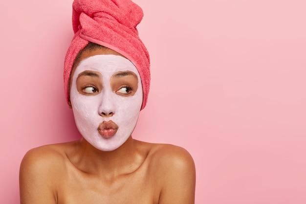 Binnenopname van een goed uitziend model met een donkere huidskleur maakt de lippen gevouwen alsof ze iemand willen kussen, draagt een voedend kleimasker, gewikkeld in een handdoek, kijkt opzij op de lege ruimte