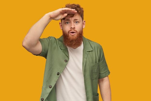 Binnenopname van een jonge, bebaarde man met een grote rode baard die naar voren kijkt met een serieuze geconcentreerde gezichtsuitdrukking