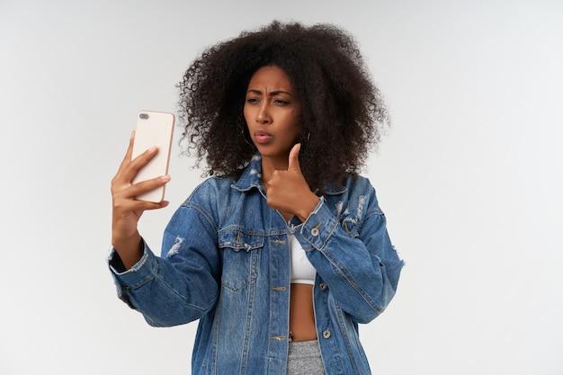 Binnenopname van een jonge, krullende, donkere dame met een casual kapsel die duim laat zien terwijl ze een foto van zichzelf maakt, met een witte top en een spijkerjasje over een witte muur