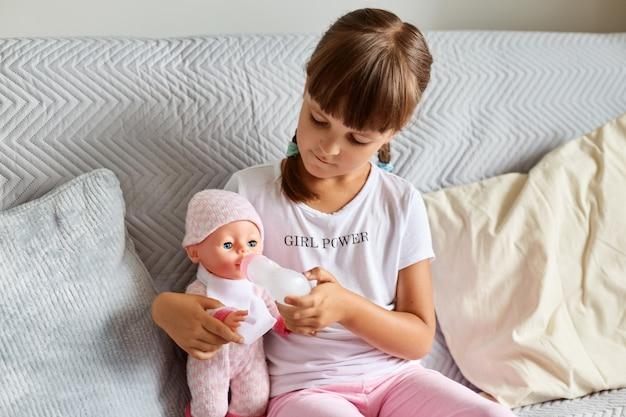Binnenopname van een klein meisje dat thuis op de bank in de kamer zit te spelen met een babypop, zoals moeder, een donkerharige kleuter die speelgoed vasthoudt.