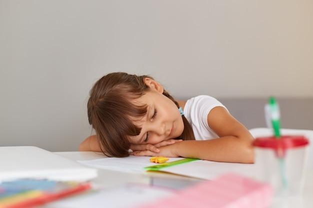 Binnenopname van een klein schoolmeisje dat slaapt terwijl ze aan tafel zit, moe is terwijl ze haar huiswerk doet, kind met donker haar dat een wit t-shirt draagt.