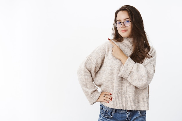 Binnenopname van een knappe charismatische jonge vrouw met bruin haar in een bril en een glimlachende trui